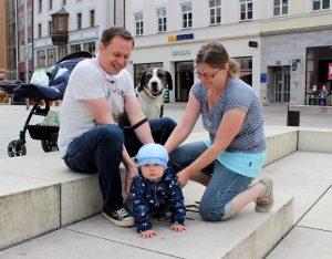 Die Maskenpflicht gilt seit 27.4. für Personen ab sechs Jahren beim Einkaufen sowie bei der Nutzung von öffentlichen Verkehrsmitteln. Der kleine Timo muss noch keine Maske tragen, da er unter sechs Jahren alt ist. Seine Eltern David und Tina sind froh, jetzt nicht mehr so abgeschottet zu sein. Die Familie hat zwar einen Balkon, aber mit Kleinkind und Hund kann es recht eng werden.