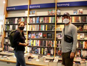 """Ihnen wäre beinahe der Lesestoff ausgegangen, doch statt bei Amazon kaufen Laura und Lukas lieber im lokalen Buchhandel. """"Es ist doch viel schöner, vor dem Bücherregal zu stehen, zu schmökern und die Bücher in die Hand nehmen zu können."""" – Stimmt!"""