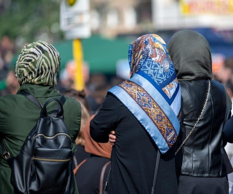 Drei Frauen im Kopftuch stehen in einer Innenstadt