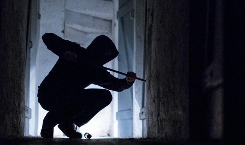 Ein Einbrecher benutzt ein Brecheisen, um eine Tür zu öffnen