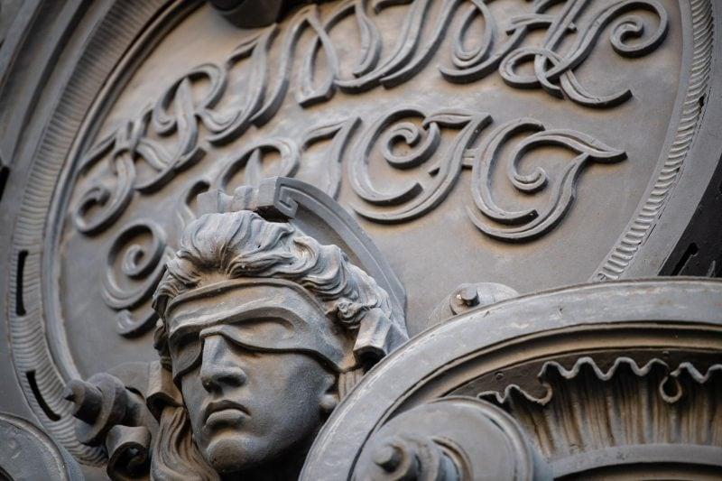 Eine Statue mit verbundenen Augen am Eingang eines Gerichts