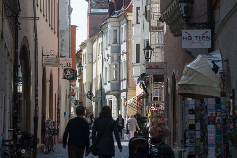 Passanten gehen durch eine Gasse in der Altstadt von Regensburg