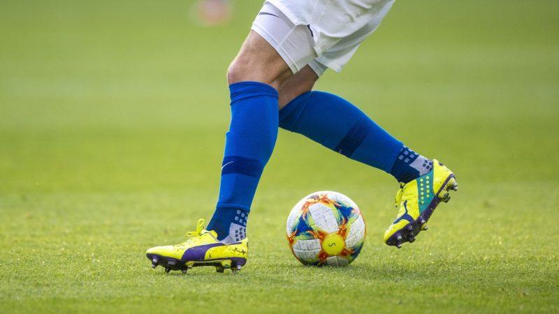 Ein Fußballspieler spielt den Ball