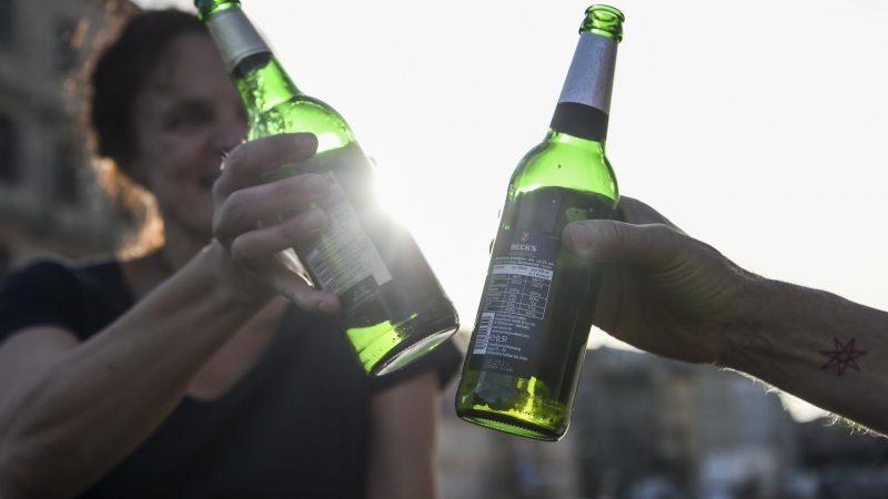Zwei Personen stoßen mit eine Bier an