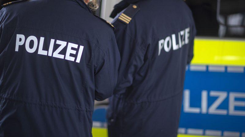 Polizeibeamte stehen vor einem Polizeifahrzeug