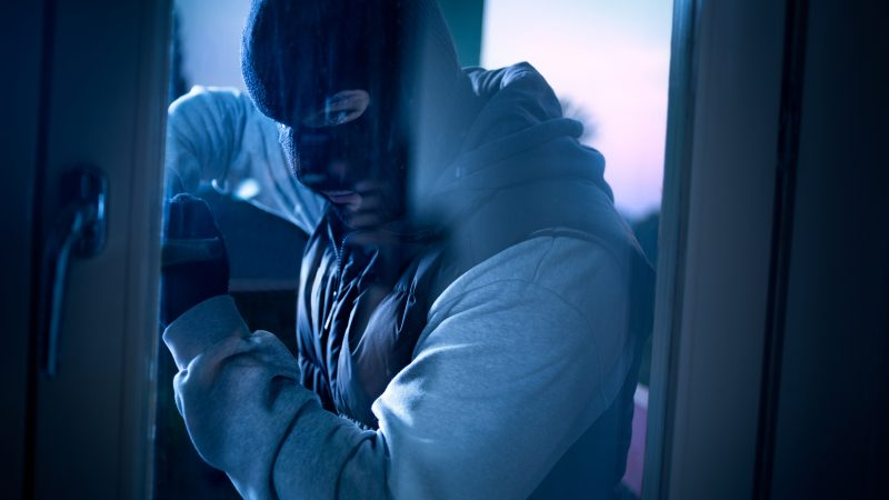 burglar with crowbar breaking into a house